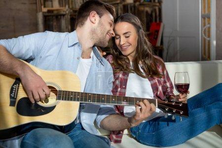 Photo pour Heureux jeune couple se reposer ensemble sur le canapé avec la guitare acoustique et vin rouge - image libre de droit