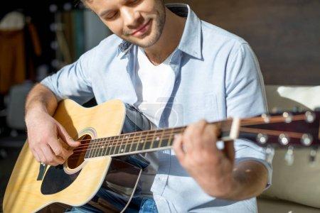 Photo pour Plan recadré de jeune bel homme jouant de la guitare et souriant - image libre de droit