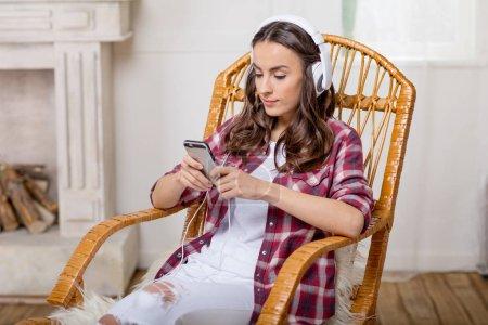 woman in headphones using smartphone