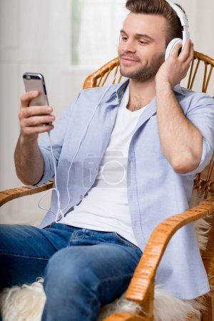 man in headphones using smartphone