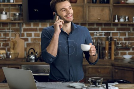 Photo for Happy young man talking on smartphone and holding coffee cup - Royalty Free Image
