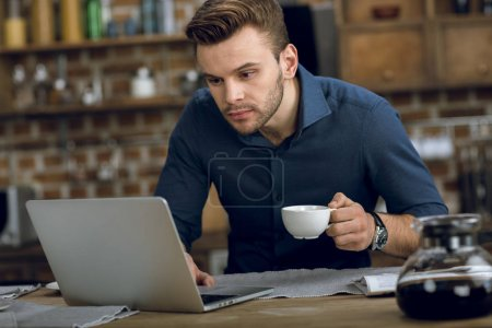 Photo for Concentrated young man using laptop while drinking coffee at home - Royalty Free Image