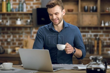 Photo for Smiling young man using laptop while drinking coffee at home - Royalty Free Image