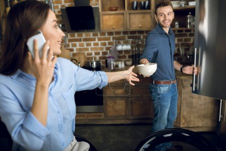 Photo for Smiling man giving bowl with breakfast to woman with smartphone - Royalty Free Image