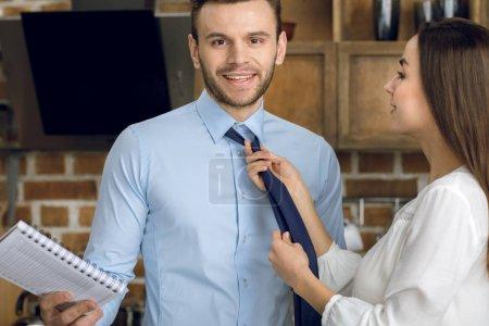 Businesswoman tying tie
