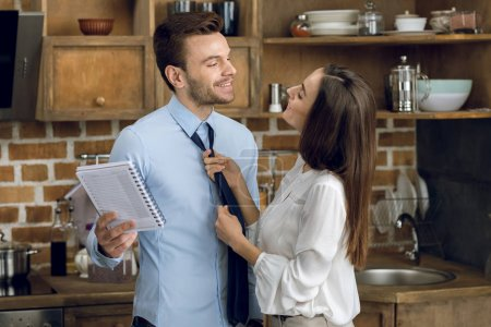 Photo for Businesswoman looking at husband and tying tie at home - Royalty Free Image