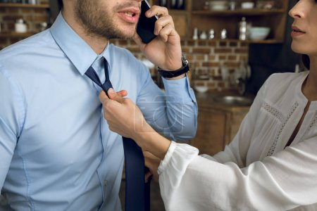 Photo for Partial view of businesswoman tying husband's tie - Royalty Free Image
