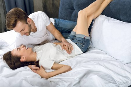 Photo for Man looking at laughing woman while lying in bed - Royalty Free Image