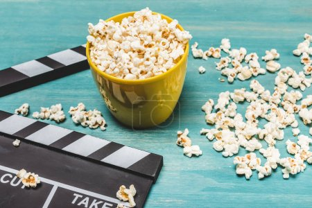Photo for Close-up view of popcorn and movie clapper on wooden table, Movie time concept - Royalty Free Image
