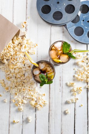 Photo for Top view of popcorn with iced tea in glasses and film reels on table, Movie time concept - Royalty Free Image