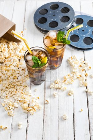 Popcorn with iced tea and film reels