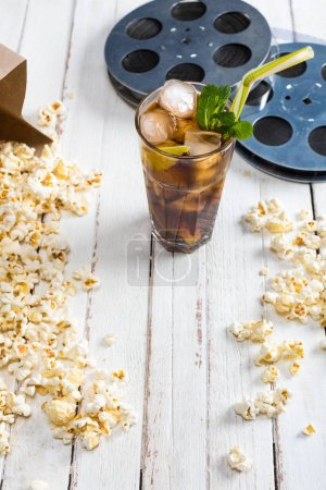 Photo for Close-up view of popcorn with iced tea in glass and film reels on table, Movie time concept - Royalty Free Image