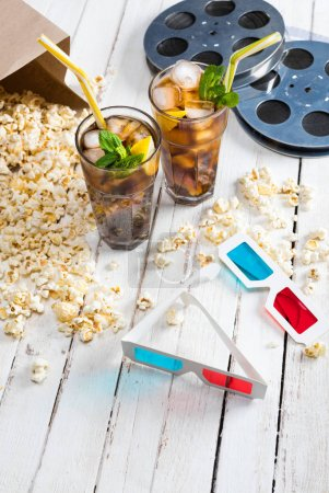 Photo for Close-up view of popcorn with iced tea, film reels and 3D glasses on table, Movie time concept - Royalty Free Image