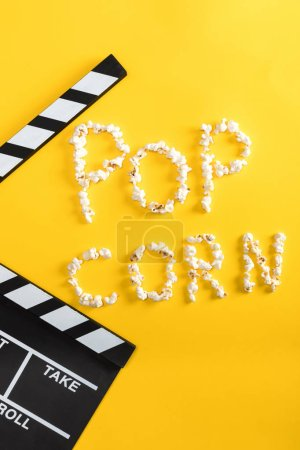 Photo for Pop corn lettering made from popcorn and movie clapper on yellow, Movie time concept - Royalty Free Image