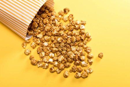 Foto de Vista superior de palomitas de maíz baja en caja en fondo amarillo - Imagen libre de derechos
