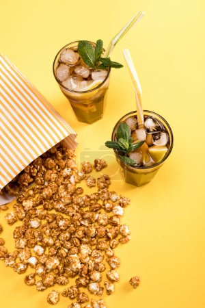 Photo for Close up view of popcorn and iced tea in glasses on yellow, Movie time concept - Royalty Free Image