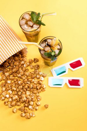 Photo for Close up view of popcorn, iced tea and 3D glases on yellow, Movie time concept - Royalty Free Image
