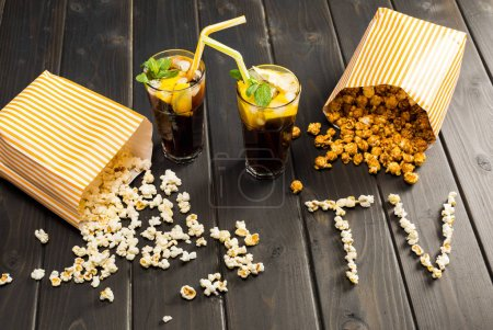 Photo for Close up view of popcorn in paper containers, drinks and tv lettering on table, tv time concept - Royalty Free Image