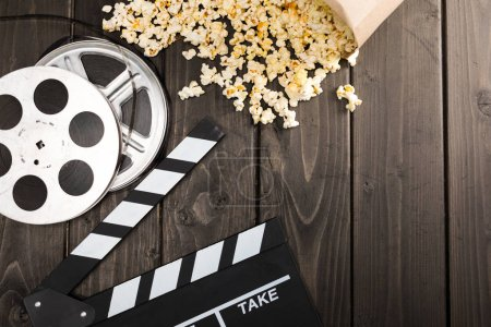 Photo pour Bouchent la vue de pop-corn en carton and film clapper board sur table, concept de temps de film - image libre de droit