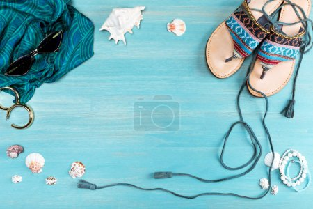Photo for Top view of sunglasses, scarf, sandals and sea shells on table - Royalty Free Image