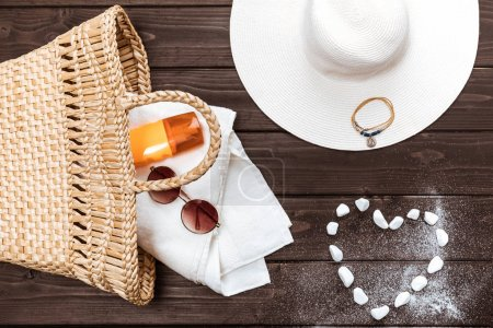 Photo for Top view of straw hat, sun cream, towel and sunglasses in bag, heart made of stones on table - Royalty Free Image