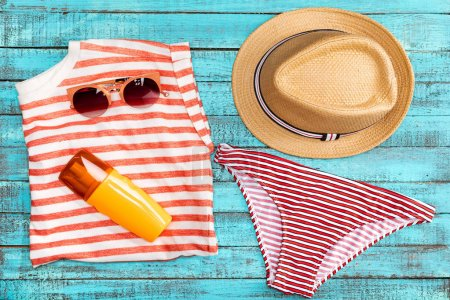 Photo for Top view of straw hat, sun cream, swimming pants and sunglasses on table - Royalty Free Image