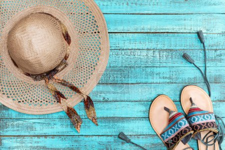 Photo for Top view of straw hat and sandals on blue wooden table, summer concept - Royalty Free Image
