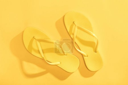 Photo for Close-up top view of comfortable yellow flip-flops on yellow background - Royalty Free Image