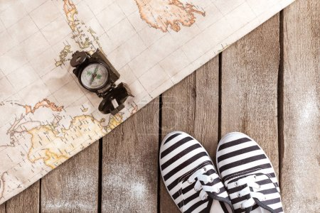 Photo for Top view of compass, world map and striped shoes on wooden table, traveling concept - Royalty Free Image