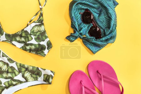 Photo for Top view of swimsuit, shawl, sunglasses and flip flops. Summer holidays concept - Royalty Free Image