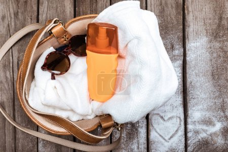 Foto de Top view of towel, sunscreen and sunglasses in bag on wooden tabletop with heart sign. Summer holidays concept - Imagen libre de derechos