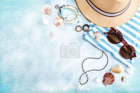 Photo for Top view of straw hat, sunglasses and striped clothes on blue tabletop with white sand. Summer holidays concept - Royalty Free Image