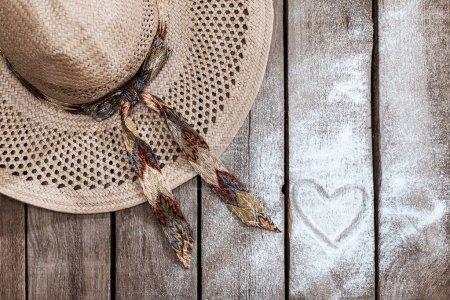 Photo pour Vue de dessus du chapeau de paille sur la table en bois avec signe de coeur. Concept vacances d'été - image libre de droit
