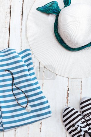 Photo for Top view of straw hat, striped clothes and sneakers on white wooden tabletop. Summer holidays concept - Royalty Free Image