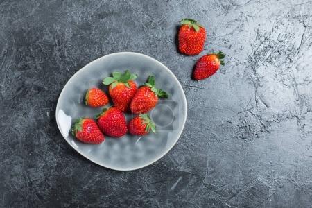 Foto de Fresas frescas rojos en placa de cerámica gris. concepto de verano, las bayas superior concepto de vista - Imagen libre de derechos