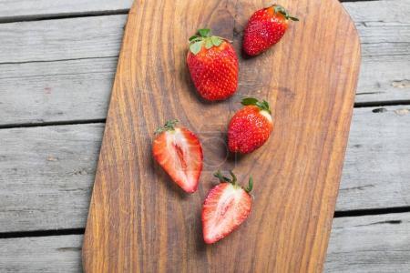 Foto de Vista superior de fresitas al rojo en la tabla de cortar madera, bayas en concepto madera - Imagen libre de derechos