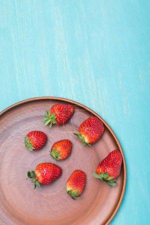 Foto de Fresas rojas sobre la placa cerámica en tablero de madera azul, bayas fondo concepto - Imagen libre de derechos