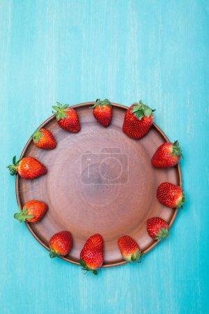 Foto de Fresas rojas frescas en círculo sobre la placa cerámica en tablero de madera azul, bayas fondo concepto - Imagen libre de derechos