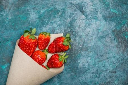 Photo for Fresh red strawberries scattered of paper cone on black tabletop, berries top view concept - Royalty Free Image