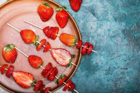 Foto de Conjunto fresas rojas y fresas en rodajas en pinchos de madera en placa de cerámica, bayas concepto vista superior - Imagen libre de derechos
