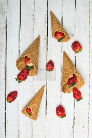 Foto de Fresas rojas dispersadas de conos de waffle en tablero de madera de blanco, bayas en concepto de madera - Imagen libre de derechos