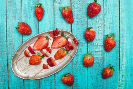 Photo pour Fraises rouges fraîches entières et fraises tranchées sur brochettes en bois dans une assiette vintage sur plateau en bois, concept de baies sur bois - image libre de droit