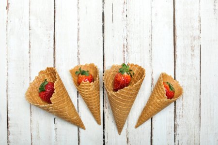 Photo for Fresh red strawberries in waffle cones on white wooden tabletop, berries on wood concept - Royalty Free Image