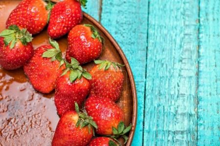 Foto de Fresas rojas frescas en plato de cerámica sobre mesa de madera turquesa, concepto de vista superior de bayas - Imagen libre de derechos