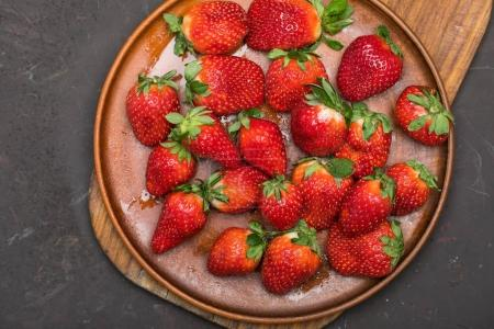 Photo for Fresh red strawberries in ceramic plate on wooden cutting board, berries top view concept - Royalty Free Image