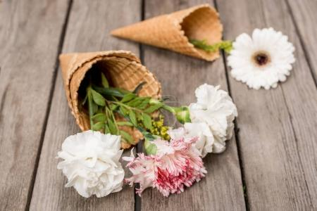 Photo for Close up of flowers in sugar cones laying on wooden table, wooden background - Royalty Free Image