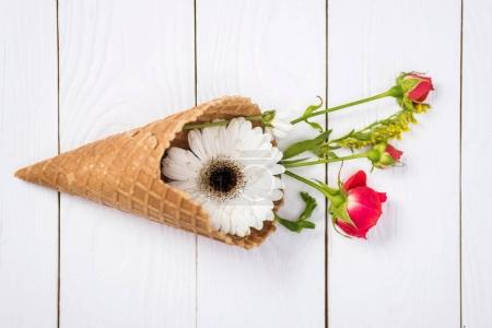 Photo for Close-up view of beautiful blossom flowers in waffle cone on white wooden background - Royalty Free Image