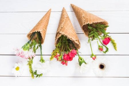 Photo for Top view of beautiful floral composition with waffle cones on wooden background - Royalty Free Image