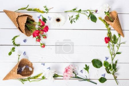 Photo for Top view of beautiful blossom flowers and green leaves in waffle cones on wooden table - Royalty Free Image