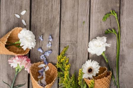 Photo for Top view of beautiful flowers and petals in wafer cones on wooden background - Royalty Free Image